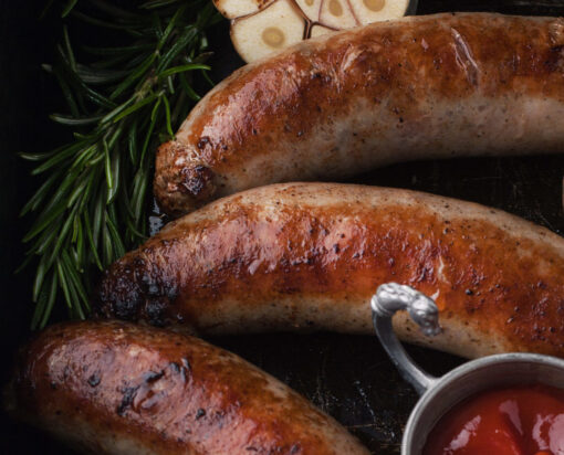 Grilled sausages on the grill with rosemary and garlic on iron pan